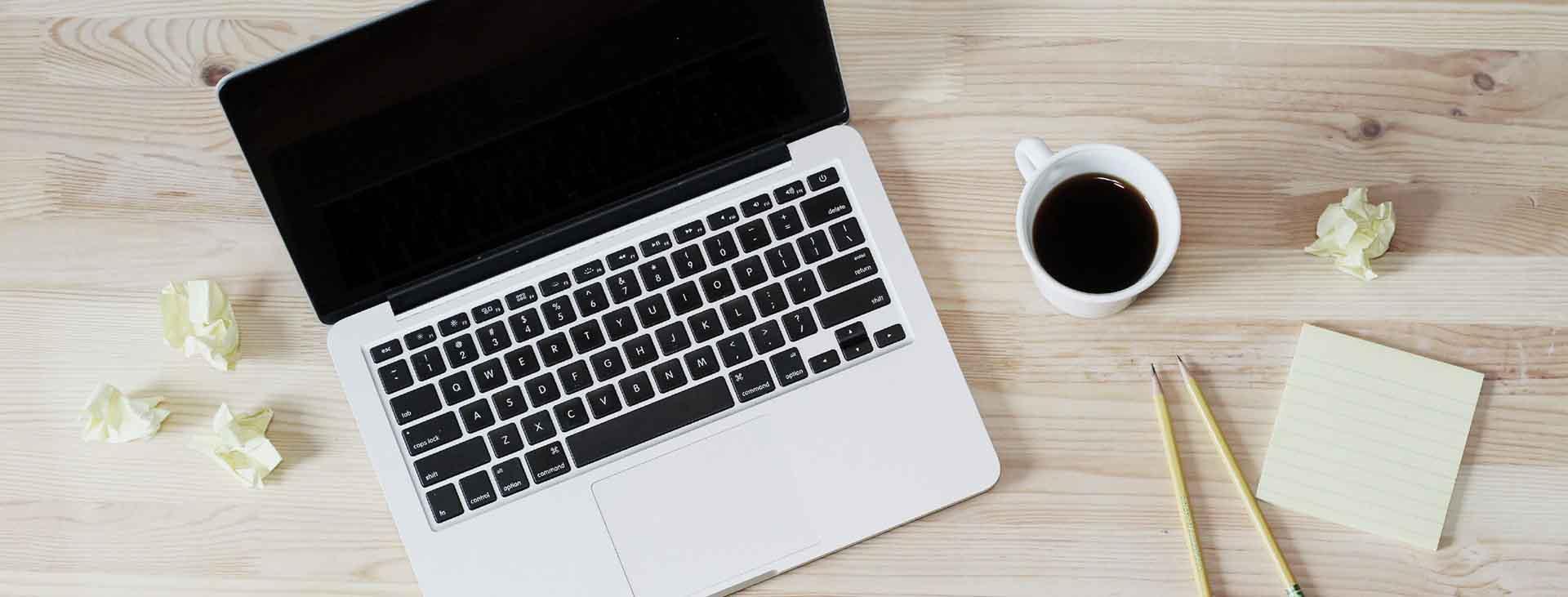 laptop met een kopje koffie op en tafel